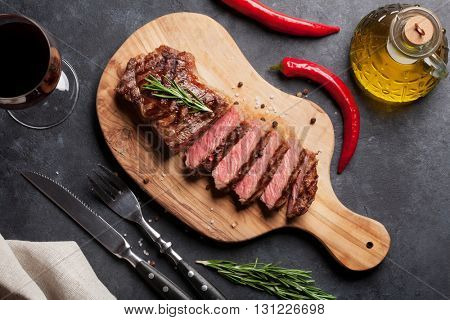 Grilled striploin sliced steak and red wine over stone table. Top view