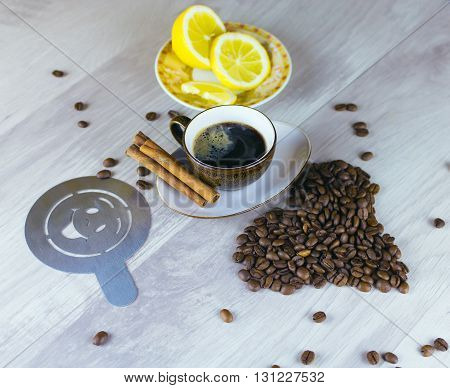 Coffee beans and coffee cup on table with lemon