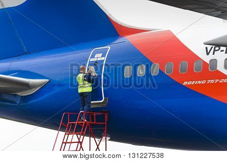 MOSCOW, RUSSIA - MAY 19, 2016: Service engineer opens the plane door Azur Air Airline Boeing 757-200.