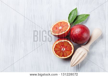 Fresh ripe red oranges and juicer on wooden table. Top view with copy space