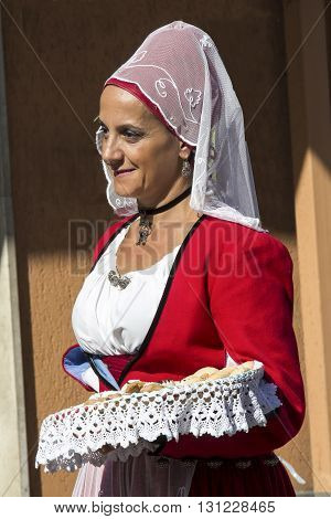 SELARGIUS, ITALY - 2014 September 14: Former marriage Selargino - Sardinia - Portrait of a beautiful woman in Sardinian costume that brings up a wicker basket with bread