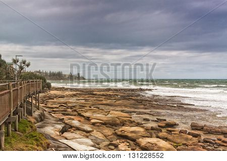 Very typical sight of the sunshine coast of Australia. The Pacific waves wash the rocks of a beach in Caloundra Queensland Australia.
