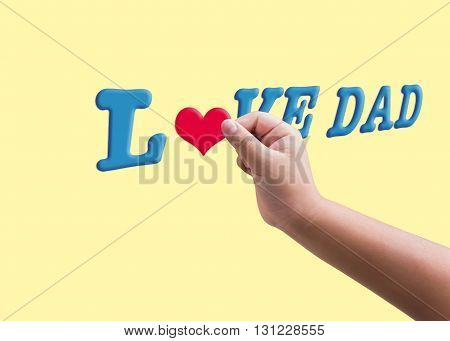 Isolated child or kid's hand hold red heard form filling to blue text love dad on yellow plain background