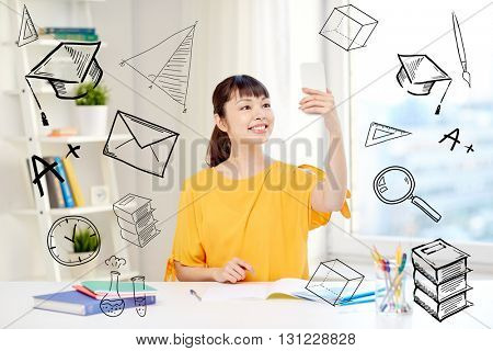 people, education, high school and learning concept - happy asian young woman student taking selfie with smartphone at home with doodles
