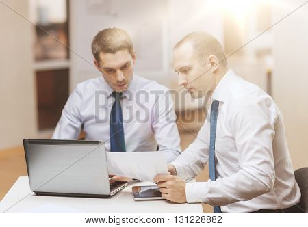 business, technology and office concept - two businessmen with laptop, tablet pc computer and papers having discussion in office
