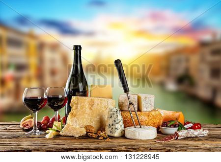 Various types of cheese, glasses and bottle of red wine placed on wooden table, copyspace for text. Blur old town on background