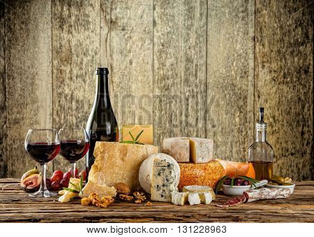 Various types of cheese, glasses and bottle of red wine placed on wooden table, copyspace for text.