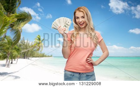 money, finances, travel, tourism and people concept - happy young woman with dollar cash money over exotic tropical beach with palm trees background