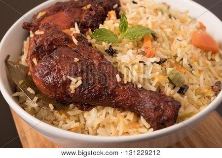Indian fried Chicken Biryani/Biriyani in a white bowl on wooden pannel