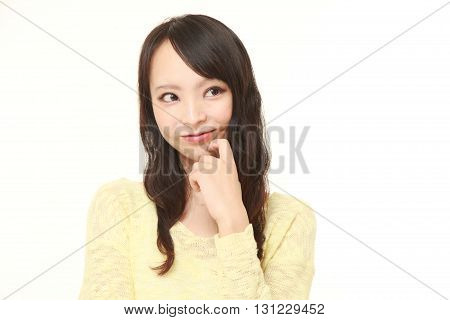 portrait of young Japanese woman thinks about something on white background