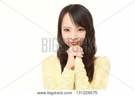 portrait of young Japanese woman folding her hands in prayer on white background