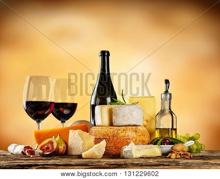 Various types of cheese, glasses and bottle of red wine placed on wooden table, copyspace for text. Abstract brown blur background
