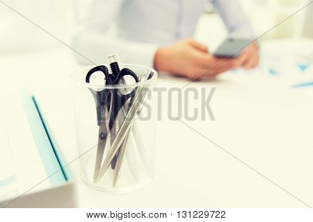 business, stationery and office supply concept - close up of organizer with scissors and pens over businessman sitting at table