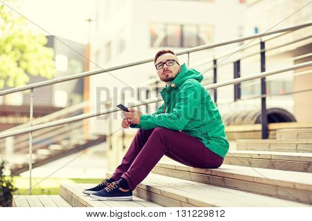 people, style, technology and lifestyle - young hipster man with smartphone sitting on stairs in city