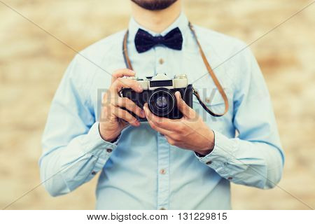 people, photography, technology, leisure and lifestyle - close up of young hipster man with retro vintage film camera on city street