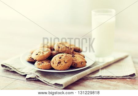 food, junk-food, culinary, baking and eating concept - close up of chocolate oatmeal cookies and milk glass on plate