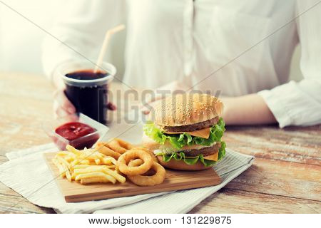fast food, people and unhealthy eating concept - close up of woman hands with hamburger or cheeseburger, french fries, squid rings and cola drink sitting at table