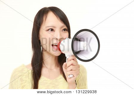 portrait of young Japanese woman with megaphone on white background