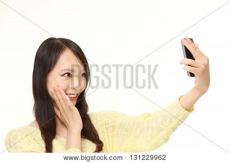portrait of Japanese woman takes a selfie on white background