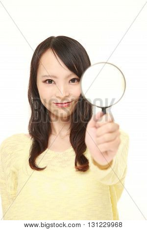 portrait of Japanese woman with a magnifying glass on white background