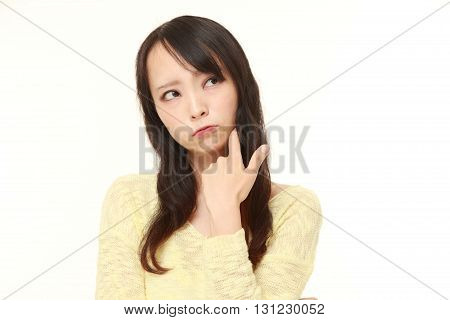 portrait of young Japanese woman worries about something on white background