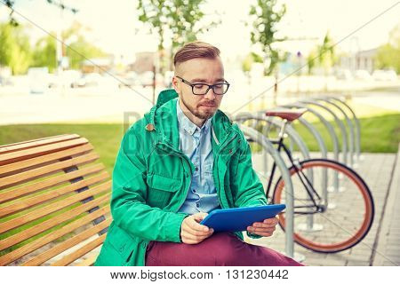 people, style, technology and lifestyle - happy young hipster man with tablet pc computer and fixie bike sitting on bench in city