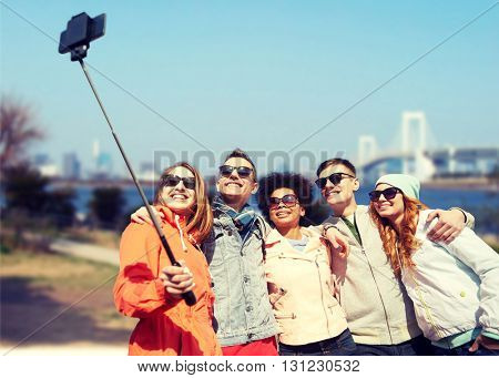 tourism, travel, people, leisure and technology concept - group of smiling teenage friends taking selfie with smartphone and monopod over rainbow bridge in tokyo city