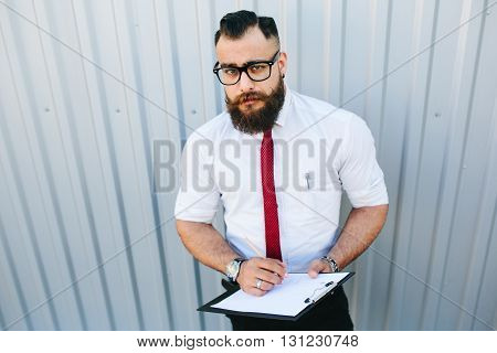 businessman stands with documents in hand against a white wall