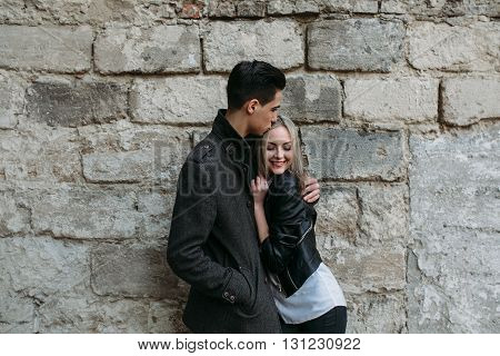Photo of a young beautiful couple on the background of the old wall