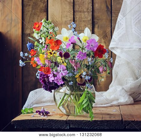 Still life with a spring bouquet in a round vase on a background of boards.