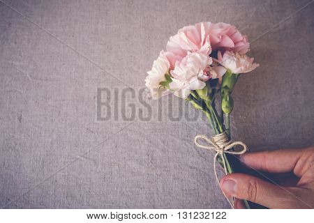 hand holding Pink carnation flowers bouquet copy space background