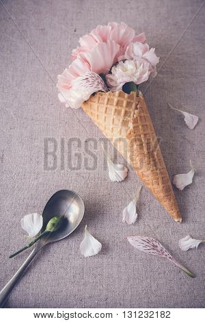Pink carnation flowers in ice cream waffle coneselective focus