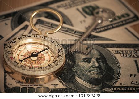 vintage compass on U.S. bank notes background.