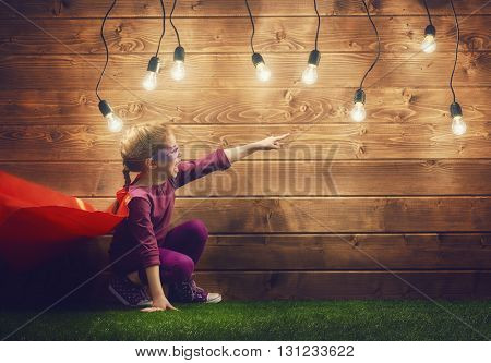 Little child girl plays superhero. Child on the background of wooden wall. Girl power concept.