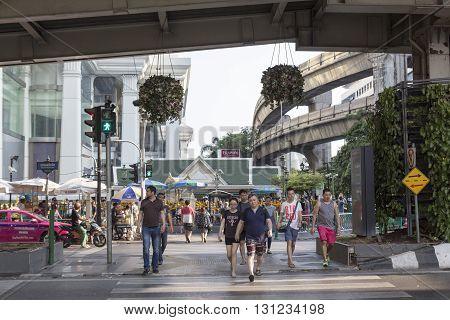 BANGKOK THAILAND - APR 17 : unidentified people walk across crosswalk near Erawan shrine at Ratchaprasong Junction on april 17 2016 thailand. Ratchaprasong Junction one of is famous landmark of Bangkok