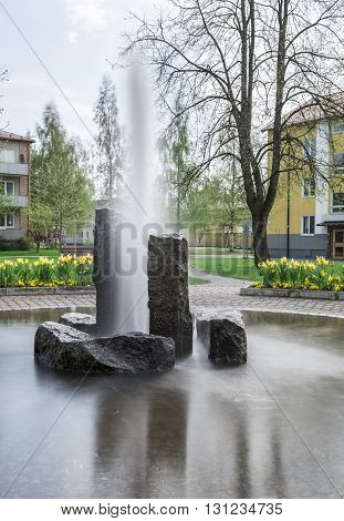 Fountain with Rocks in residential area with flowers.