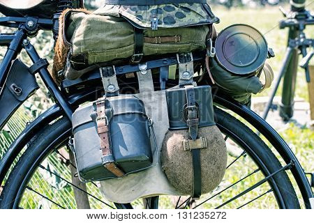 Close up photo of old military bicycle with equipment. Backpack and containers for food and drink. Vintage scene. Retro transport. Equipment of german soldier in World War II.
