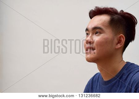 Young asian man looking hopeful smiling at a direction