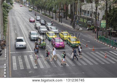 BANGKOK THAILAND - APR 17 : unidentified people walk across crosswalk at Ratchaprasong Junction near Erawan shrine on april 17 2016 thailand. Ratchaprasong Junction one of is famous landmark of Bangkok