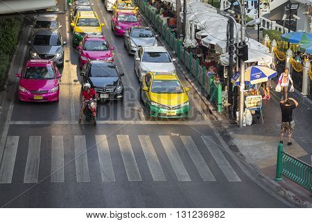 BANGKOK THAILAND - APR 17 : cars stop for red light signal on traffic in Ratchaprasong Junction near Erawan shrine on april 17 2016 thailand. Ratchaprasong Junction one of is famous landmark of Bangkok