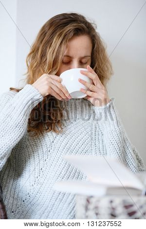 Young Woman Drinking Coffee Or Tea In Cafe