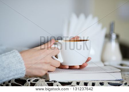 Cup Of Coffee In Female Hands Closeup And Book On Table