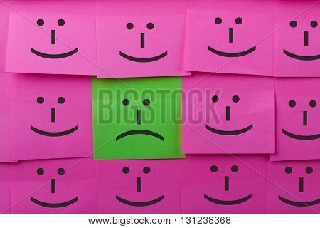 Unhappy and happy concept. Background of sticky notes. Green sticky note is among pink sticky notes.