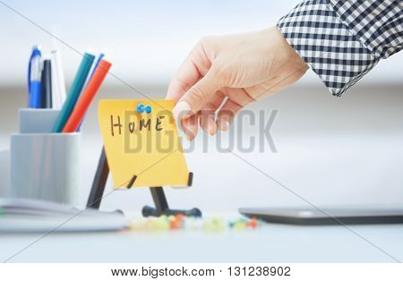 Human hand holding adhesive note with Home text