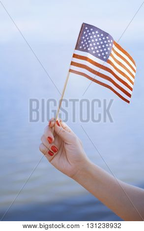 Woman hand holding USA flag in front of the ocean