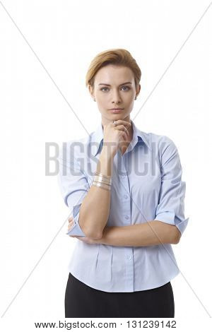 Portrait of serious businesswoman standing hand on chin, looking at camera.