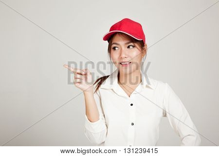 Happy Asian Girl With Red Hat Point To Blank Space