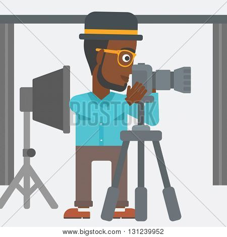 An african-american photographer working with camera on the background of photo studio with lighting equipment vector flat design illustration. Square layout.