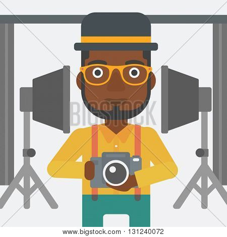 An african-american man holding a camera on the background of photo studio with lighting equipment vector flat design illustration. Square layout.
