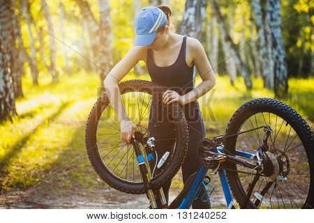 woman repair her bicycle in the forest